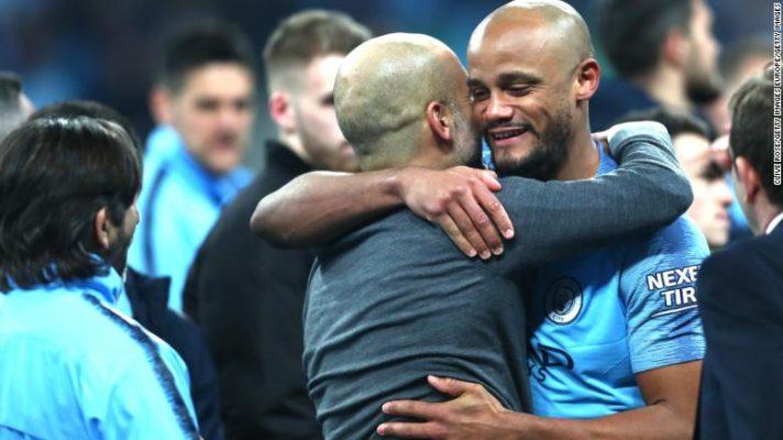 City manager Pep Guardiola exchanges a hug with defender Vincent Kompany.