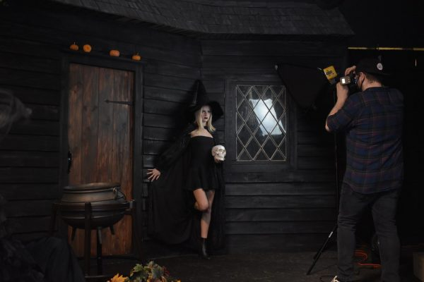 A masked photographer taking a photo of a customer in a witch costume